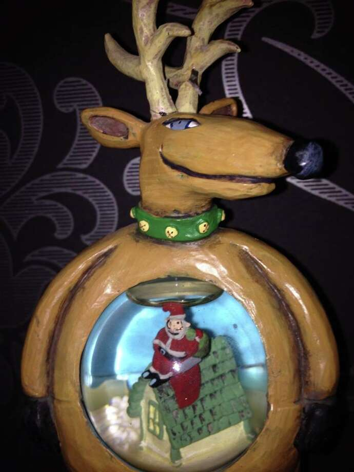 Janet Blackburn: This snow globe reindeer is one of our family's most cherished Christmas decorations.  His creepy expression and his rotund belly that seemingly indicates that he swallowed Santa makes him the kids favorite.  We won him a few years ago on Christmas day at our family celebration.  Every year we try and guess when my punctuality challenged sister might show up.  It's all in good fun, and she can also win the drawing if her assigned time slot is chosen.   The prize is always an ugly decoration, a pooping reindeer, a Yeti stocking, or something equally as unusual.    Enjoy!
