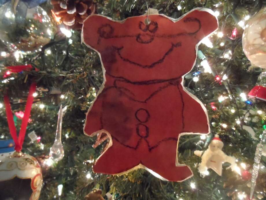 """S. Darlene Peaks, League City: When our daughter, Nicole was about five, she made a bear ornament in school from red construction paper. It was crooked and had a lopsided, drawn on smile! She was sooo proud of it and I loved it! That Christmas, I was missing my Dad, who had recently passed away. As I began to decorate the tree, there was that bear…grinning broadly in her hand! All my sadness disappeared? It has hung on the tree every year for 30 plus years! One year, it got damp in storage and a little mildew caused dark spots. She didn't want us to hang it up, but I convinced her it wouldn't be Christmas without it. She got some clear shelf paper and """"laminated"""" it! It is not perfect, but neither is life.  That bear still touches my heart and brightens my holiday every year!"""