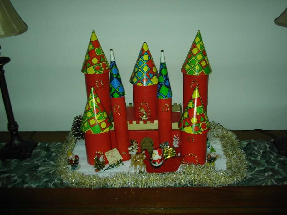 "Mary Connell, The Woodlands: One of my favorite decorations is the Christmas Castle. My entire family made various pieces of it when I was in the fourth grade in the early 1970s near Hartford, Connecticut.  It is made from large and small tin cans, a shoe box and a cake mix box, all covered in adhesive red paper (we called it Contact paper). Even my dad, who didn't usually do any Christmas decorating, got into the act and made the balcony by cutting the ""dental work"" from the top of a shoe box.  The rooftops are made of birthday party hats and party blowers. Other features are made of different types of tinsel and ornaments. Some years we used Andes mints for the gifts in the sleigh. Every year we put it on the kitchen counter where it was always in the way, but we always loved it. If you walked by too fast, or shut a door too hard, the party hats would topple off and have to be put back or readjusted.  It didn't matter, though—the handwritten sign said it all: ""Santa's North Pole Castle—this is Santa's home.""  For a number of years, we placed a glitter-covered Santa on the balcony. Over the years, he lost his glitter, and became ""Naked Santa,"" which lent itself to a number of laughs and jokes.   Somehow, as the years passed,  ""Naked Santa"" was lost to time and history, as were Mom and Dad, the kitchen where the castle was created and many of the special times and relationships that Christmas memories conjure up.  The castle probably should have gone to the recycling bin years ago, but instead spends most of its time in a closet in The Woodlands, Texas, and once a year (or every other year), I bring it down and place it lovingly and excitedly on a buffet table in the living room. I think my husband is somewhat embarrassed by it, but he lets me enjoy it each time without complaint because he understands the connection, falling party hats and all.  For a few days, especially in the evening when the lights are low and the old tinsel around the castle reflects the twink"