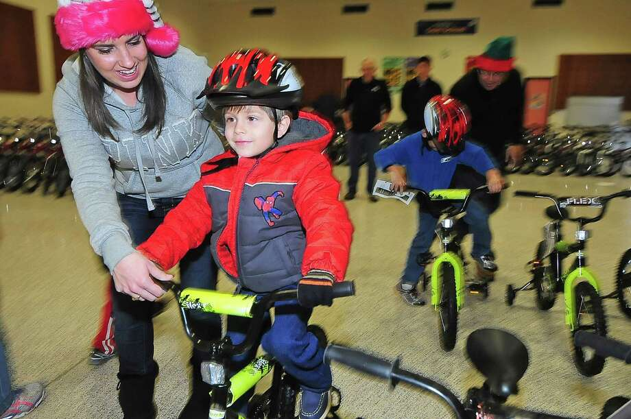 Klenk Elementary third-grade teacher Stephanie Cole helps Jordan Insua pick out the perfect bicycle during a Christmas bike giveaway for deserving pupils held Dec. 14 at the school. Photo: Â Tony Bullard 2013, Freelance Photographer / © Tony Bullard & the Houston Chronicle