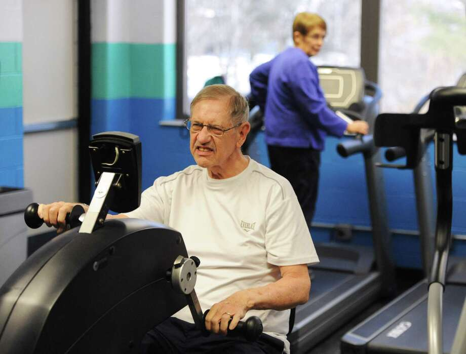 Jim Walsh works out on the upper body cycle machine as his his wife, Susan Walsh, walks on the treadmill behind him at the Greenknoll YMCA in Brookfield, Conn. on Friday, Dec. 20, 2013.  Jim is a two-time kidney transplant recipient and received his second transplant from his wife two years ago.  They are telling their story to help the YMCA raise money in their annual campaign. Photo: Tyler Sizemore / The News-Times