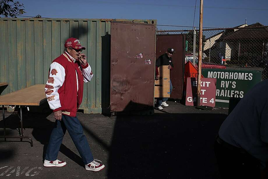 Walt Daoro, left, smokes his cigar as he prepares to tailgate before the game at Candlestick Park on Monday, Dec. 23, 2013. The San Francisco 49ers hosted the Atlanta Falcons at one of their last games at Candlestick Park. Photo: James Tensuan, Special To The Chronicle