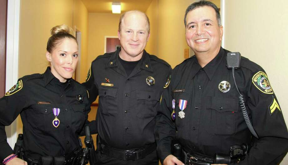 Selma Police officers Tiffany Kierum and Jesus Balderamas, right, received letters of commendation Dec. 12 from Selma Police Chief Syd Hall, center. Kierum and Balderamas were shot while responding to a domestic disturbance call. Photo: Courtesy Photo / Paul Gumm Photography