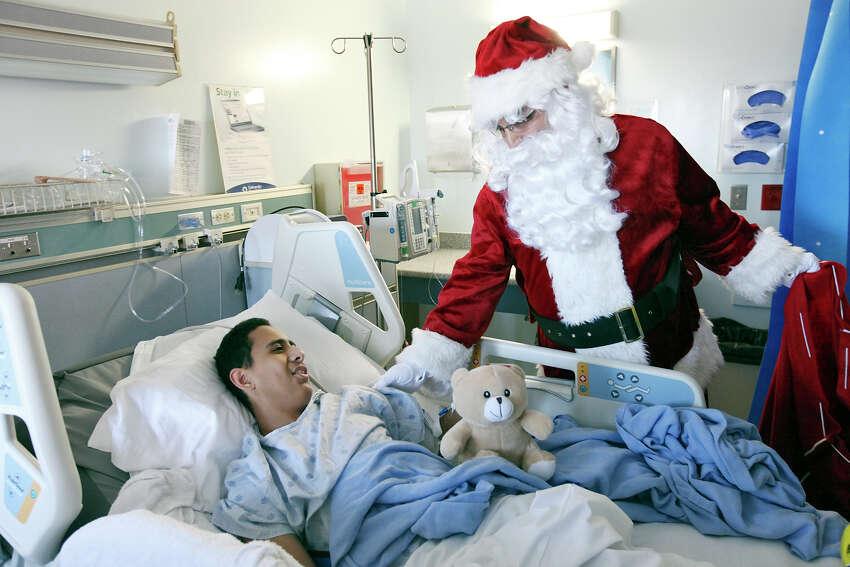 Left: Eugenio Gonzalez, 14, talks with Santa after receiving a teddy bear Monday Dec. 23, 2013 at University Hospital.