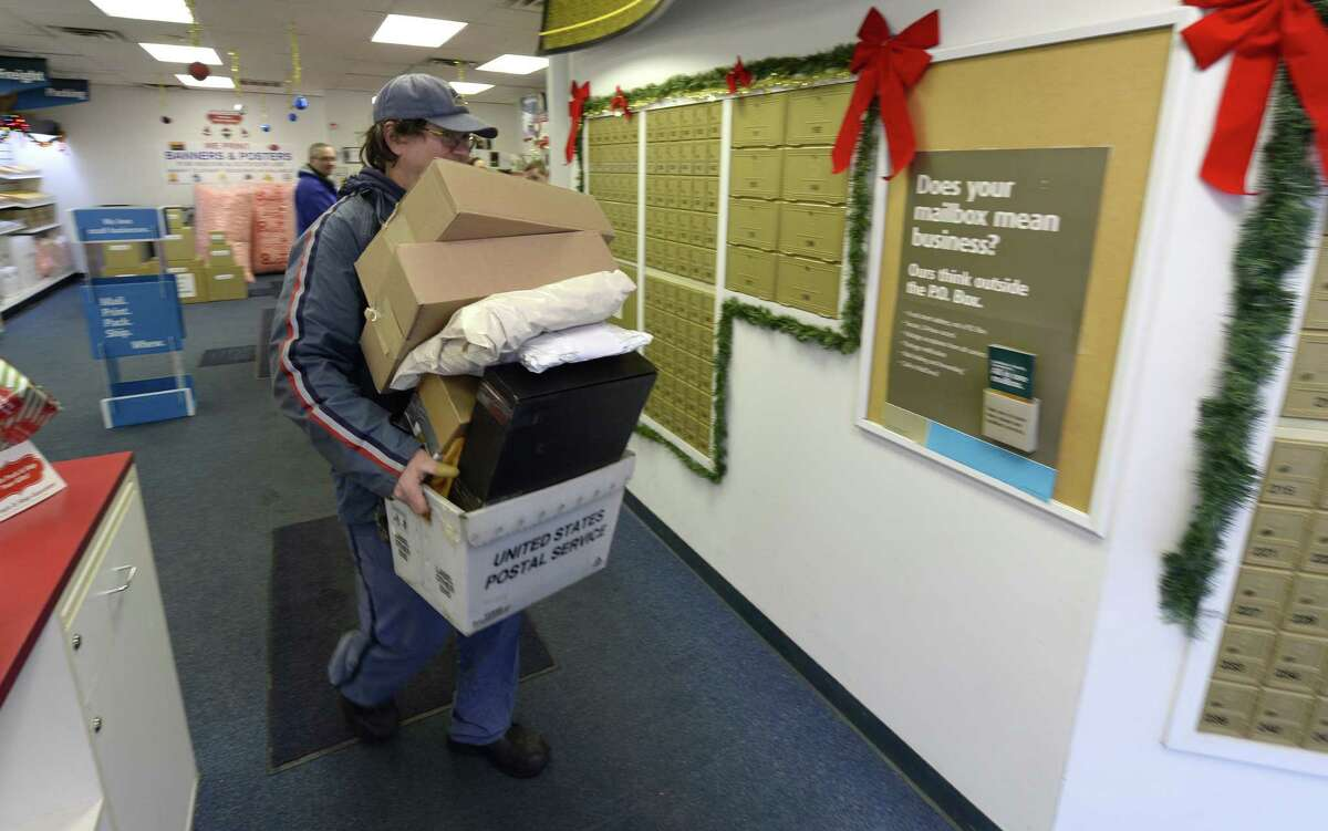 Munawar Din, left, a customer service person assists Mhung Ngo, right, in packaging up a last minute gift that will be shipped from the Colonie Center USPS mail facility Monday, Dec. 23, 2013, in Colonie, N.Y. (Skip Dickstein / Times Union)