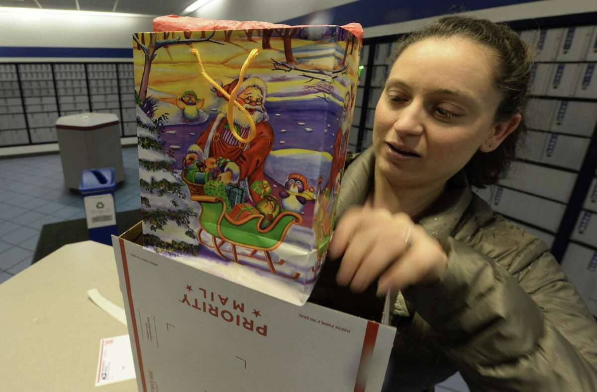 Jessica Smith, formerly of Altamont and now living in Indiana, packages a last minuet Christmas gift Monday, Dec. 23, 2013, at the USPS mail facility in Colonie, N.Y. (Skip Dickstein / Times Union)