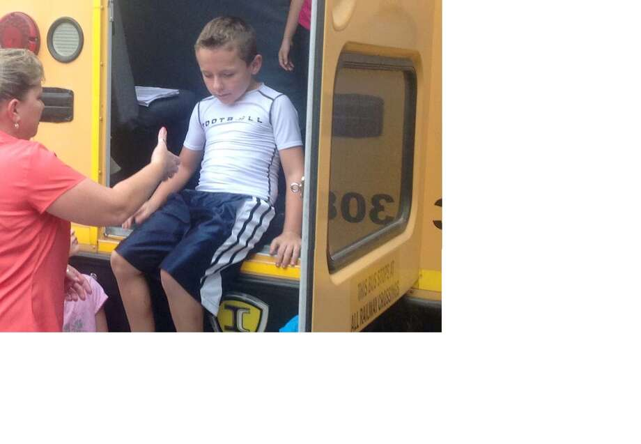 Bus driver Angela Rex helps second-grade student Reece Lee from a rear exit during a Tomball Elementary School safety drill. Photo: Provided By Tomball Elementary School