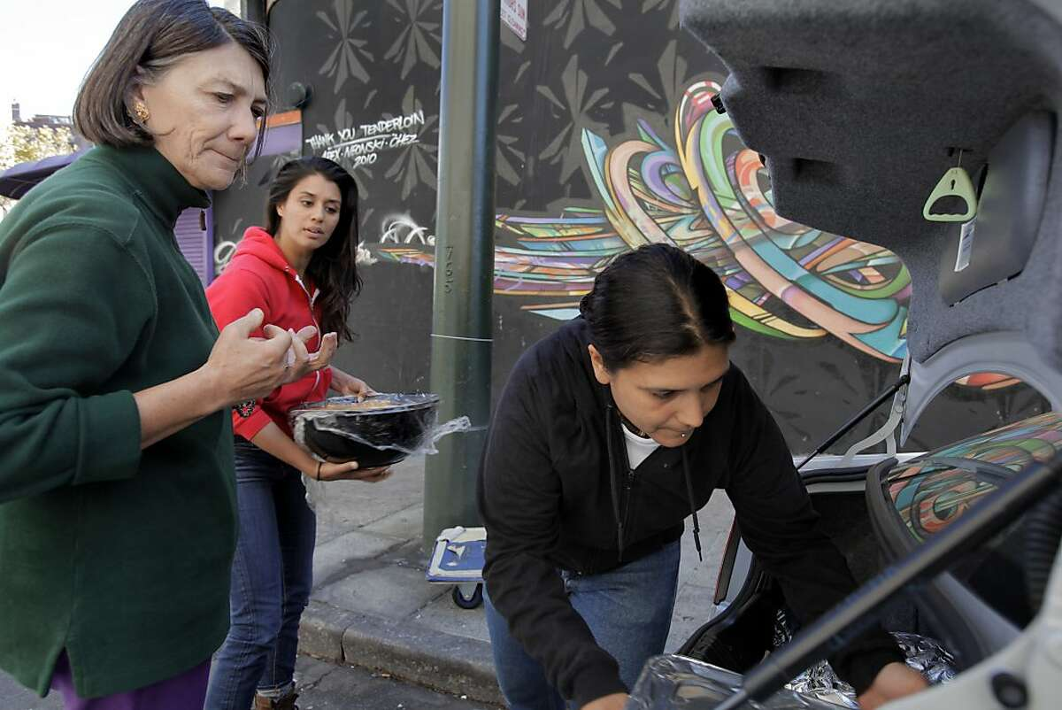 Alexandra Vuksich, left, drops off food to Alya Briceño, right, and Jenni Jain, center for the UFO Study in the Tenderloin of San Francisco, Calif., on Wednesday, September 25, 2013. Vuksich picked up the food at Squar and delivered it to local services for the poor on Wednesday, September 25, 2013.