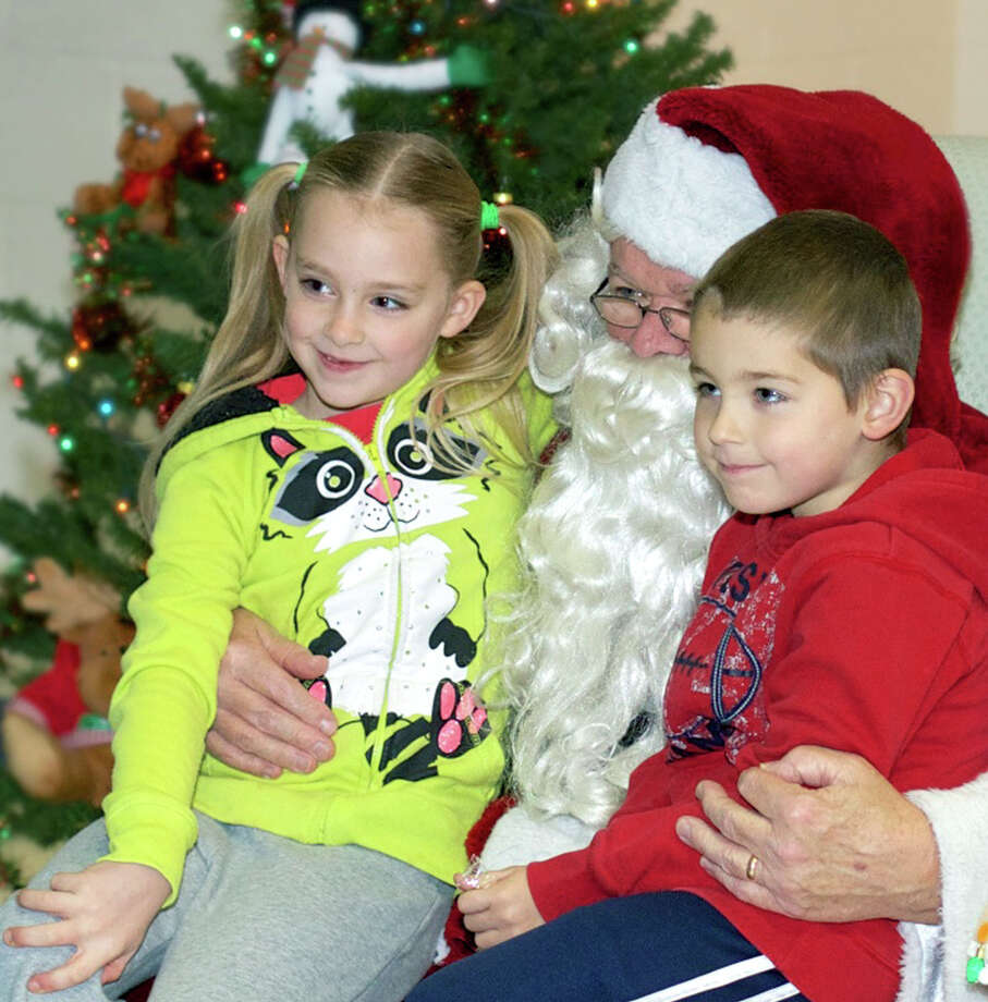 "Jolene Spahn, 7, and her brother, Braydon, 5, of New Milford are living the dream as they pose for a photo on Santa Claus' lap during ""Breakfast With Santa,"" Sarah Noble Intermediate School's traditional holiday fundraiser hosted by the BandAides for the school's band. Dec. 8, 2013 Photo: Trish Haldin / The News-Times Freelance"