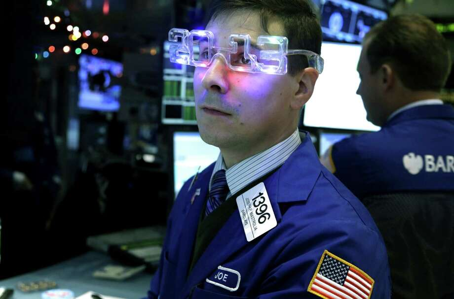 "FILE - In this Monday, Dec. 31, 2012, file photo, a trader wearing ""2013"" glasses works on the floor at the New York Stock Exchange in New York. While 2013 was a great year for the average investor, few market strategists believe that 2014 will be anywhere near as good. (AP Photo/Seth Wenig, File) ORG XMIT: NYBZ205 Photo: Seth Wenig / AP"