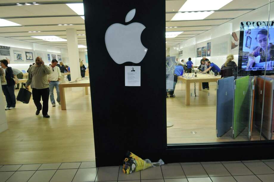 A bouquet of flowers and a written memorial to the late Steve Jobs are outside of the Apple Store at Crossgates Mall on Thursday Oct. 6, 2011 in Guilderland, NY.  The Apple co founder died on Wednesday. A store employee said that the apple logos outside of the store weren't lit, for the first time in his memory. ( Philip Kamrass / Times Union) Photo: Philip Kamrass / 00014892A