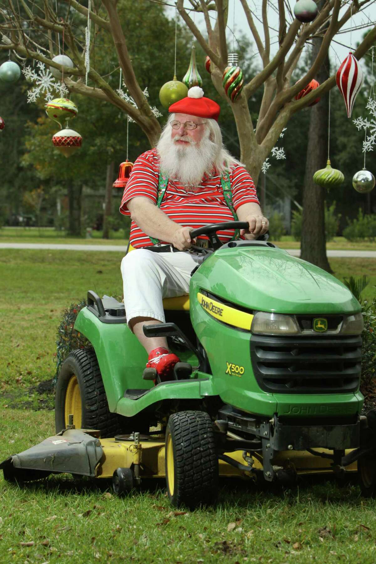 (For the Chronicle/Gary Fountain, December 20 2013) Santa Jim Fletcher on his John Deere lawnmower. Jim said that he occasionally makes a short-term trade of his reindeer for the John Deere. Jim isn't just Santa Claus in the weeks before Christmas. His white beard is year round, and during the year he attends Claus classes and conventions.