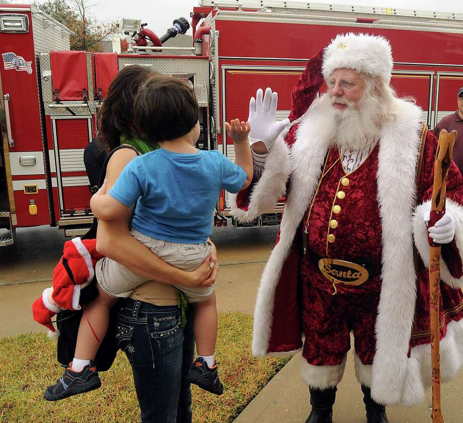 """Santa Jim Fletcher get a high five from a young admirer. The Lone Star Santas co-founded by Fletcher are """"third responders"""" who have Red Cross training. Photo: Dave Rossman, Freelance / © 2013 Dave Rossman"""