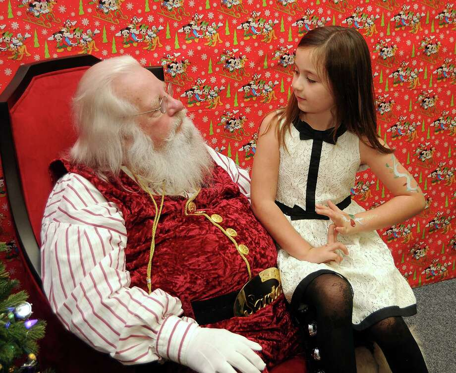 Isabella Prineaux,7, talks toys with Santa Jim Fletcher during his appearance at the Cypress Mill Recreation Center Saturday Dec. 21, 2013. (Dave Rossman photo) Photo: Dave Rossman, Freelance / © 2013 Dave Rossman