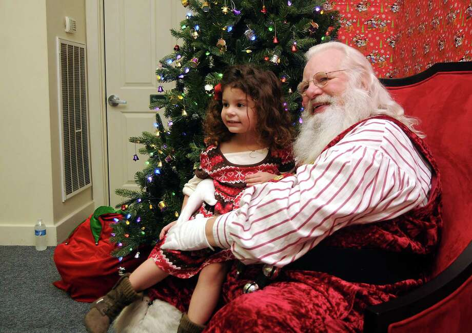 Mia Quiros,3, has her picture taken with Santa Jim Fletcher during his appearance at the Cypress Mill Recreation Center Saturday Dec. 21, 2013. (Dave Rossman photo) Photo: Dave Rossman, Freelance / © 2013 Dave Rossman
