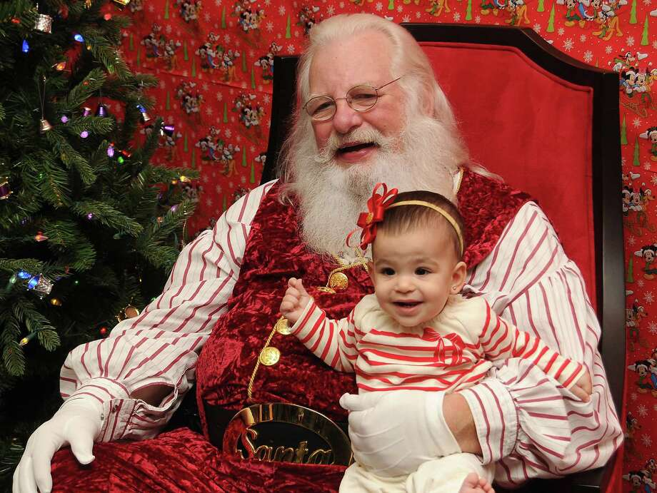 Ixa Jaeger,9 months, has her picture taken with Santa Jim Fletcher during his appearance at the Cypress Mill Recreation Center Saturday Dec. 21, 2013. (Dave Rossman photo) Photo: Dave Rossman, Freelance / © 2013 Dave Rossman
