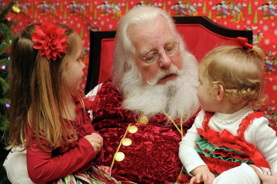 Brooke,4, and Sommer Davis, age 23 months, tell  Santa Jim Fletcher their Christmas wishes during his appearance at the Cypress Mill Recreation Center Saturday Dec. 21, 2013. (Dave Rossman photo) Photo: Dave Rossman, Freelance / © 2013 Dave Rossman