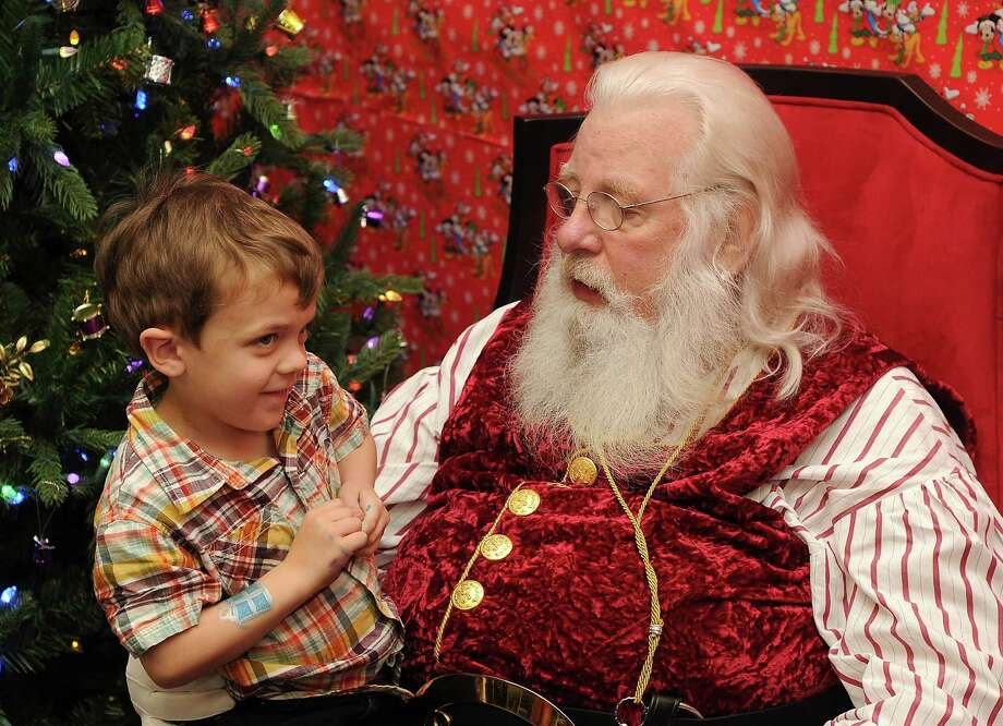 A shy John Merrill tells Santa Jim Fletcher what he wants for Christmas during his appearance at the Cypress Mill Recreation Center Saturday Dec. 21, 2013. (Dave Rossman photo) Photo: Dave Rossman, Freelance / © 2013 Dave Rossman