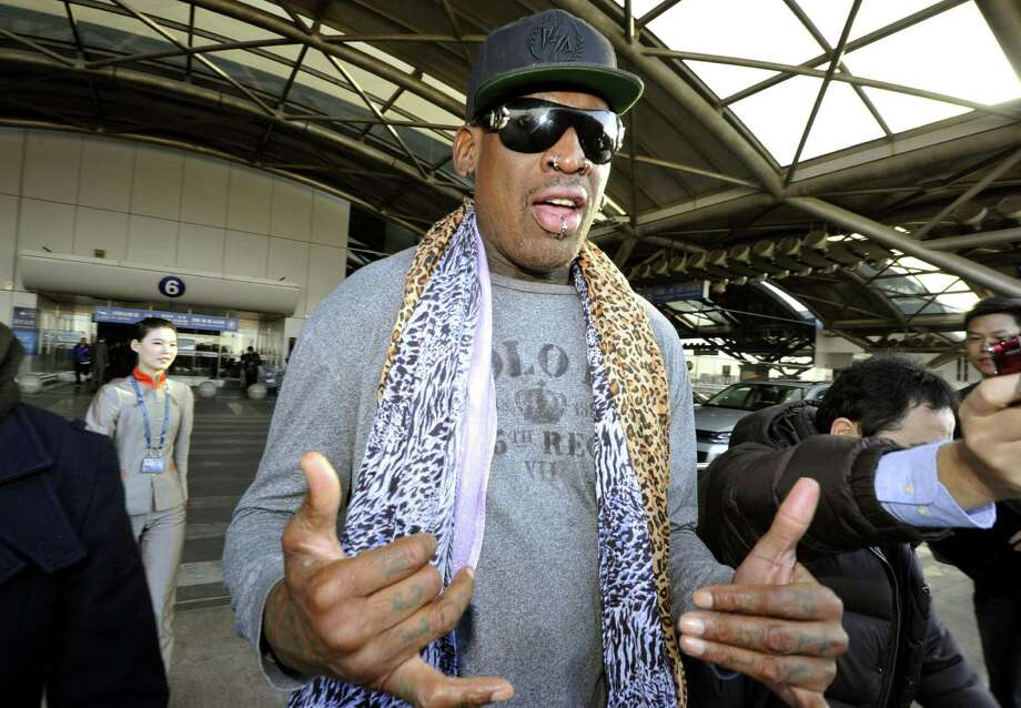 Former basketball star Dennis Rodman speaks to journalists upon arrival at the capital airport in Beijing from Pyongyang, North Korea, Monday, Dec. 23, 2013. Rodman left North Korea on Monday, but didn't answer questions from the media on whether he had met with leader Kim Jong Un on his latest visit. The two struck up a friendship when Rodman first traveled to the secretive state earlier this year. (AP Photo/Kyodo News) JAPAN OUT, CREDIT MANDATORY ORG XMIT: TOK801 / Kyodo News