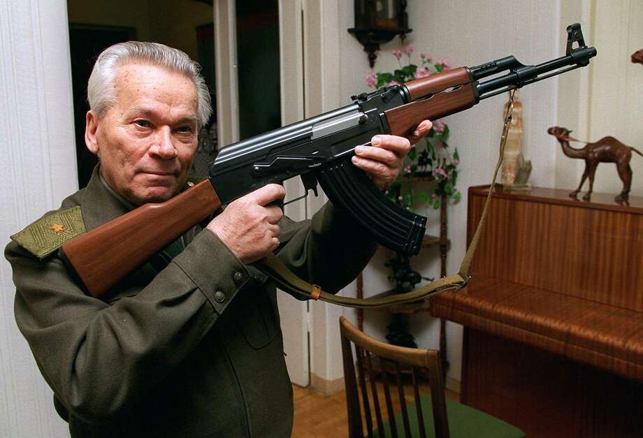 In this 1997 file photo, Mikhail Kalashnikov shows a model of his world-famous AK-47 assault rifle at home in the Ural Mountain city of Izhevsk. Photo: Vladimir Vyatkin, STR / AP