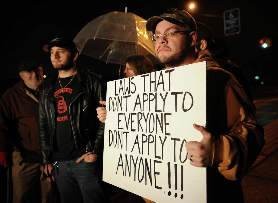 James Keyser, right, of Bridgeport, leads a small rally outside police headquarters on Congress Street in Bridgeport, Conn. on Monday, December 23, 2013 to protest what he says is preferential treatment of Bridgeport police officer Juan Santiago who fired a gun in a crowded Bagel King restaurant on Main Street in Bridgeport on December 17. Photo: Brian A. Pounds / Connecticut Post