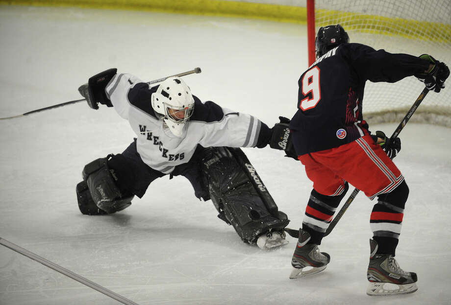 Staples goalie Will Englehart makes a pad save on a shot by New Fairfield Immaculate's Austin Murphy in the second period of their game at the Milford Ice Pavilion in Milford, Conn. on Monday, December 23, 2013. Photo: Brian A. Pounds / Connecticut Post