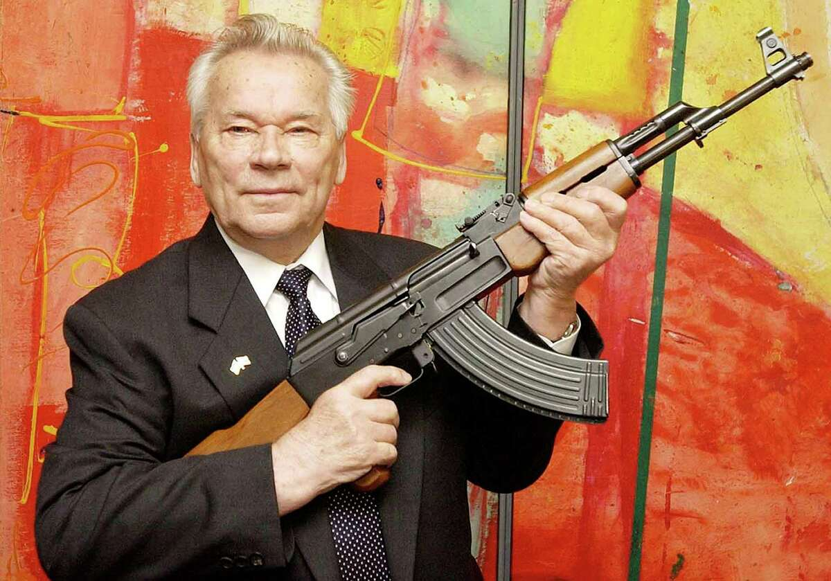FILE - In this July 26, 2002 file photo, Russian weapon designer Mikhail Kalashnikov presents his legendary assault rifle to the media while opening the exhibition