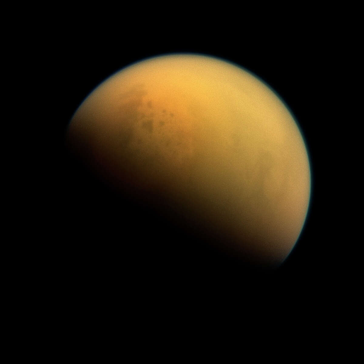 This image provided by NASA shows the hazy atmosphere of Saturn?'s moon, Titan. NASA?'s Cassini spacecraft was able to peer through the haze and spot lakes made up of hydrocarbons. The view was acquired at a distance of approximately 809,000 miles (1.303 million kilometers) from Titan. Image scale is 5 miles (8 kilometers) per pixel. (AP Photo/NASA/JPL-Caltech/Space Science Institute) ORG XMIT: LA114