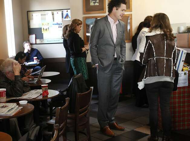 Bret Bocook, center, takes a moment to talk to a woman who preferred not to give her name about the dangers of talking on your cellphone next to your ear in a Starbucks on Main Street in Los Altos. Bocook believes that the malignant brain tumor he was diagnosed with almost five years ago was caused by his years-long cellphone use. Bocook often goes out of his way in public places to warn people about what he believes to be the dangers of cellphone usage and improper storage. Bocook used to be extremely physically active, but after the tumor was removed, many of his motor functions were effected. He now walks with a walking stick and is unable to do any of the athletic things he used to enjoy like rowing. Bocook was in commercial real estate before he decided to become a lawyer 15 years ago. He is now one of three plaintiffs left in an original group of ten people in lawsuit against cellphone companies. Bocook now runs a geo-political social networking and international law firm online company called World'sLaw.com. Photo: Leah Millis, The Chronicle