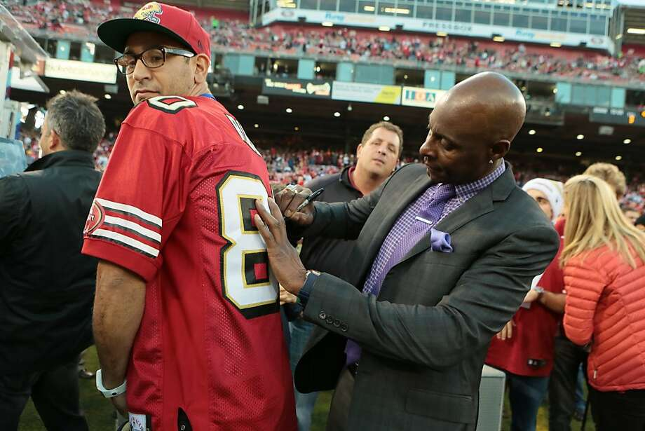 Former San Francisco 49er Jerry Rice, right, signs Robert Santini's jersey prior to the start of Monday night's game at Candlestick Park on Monday, Dec. 23, 2013 in San Francisco, Calif. Photo: John Storey, For The Chronicle