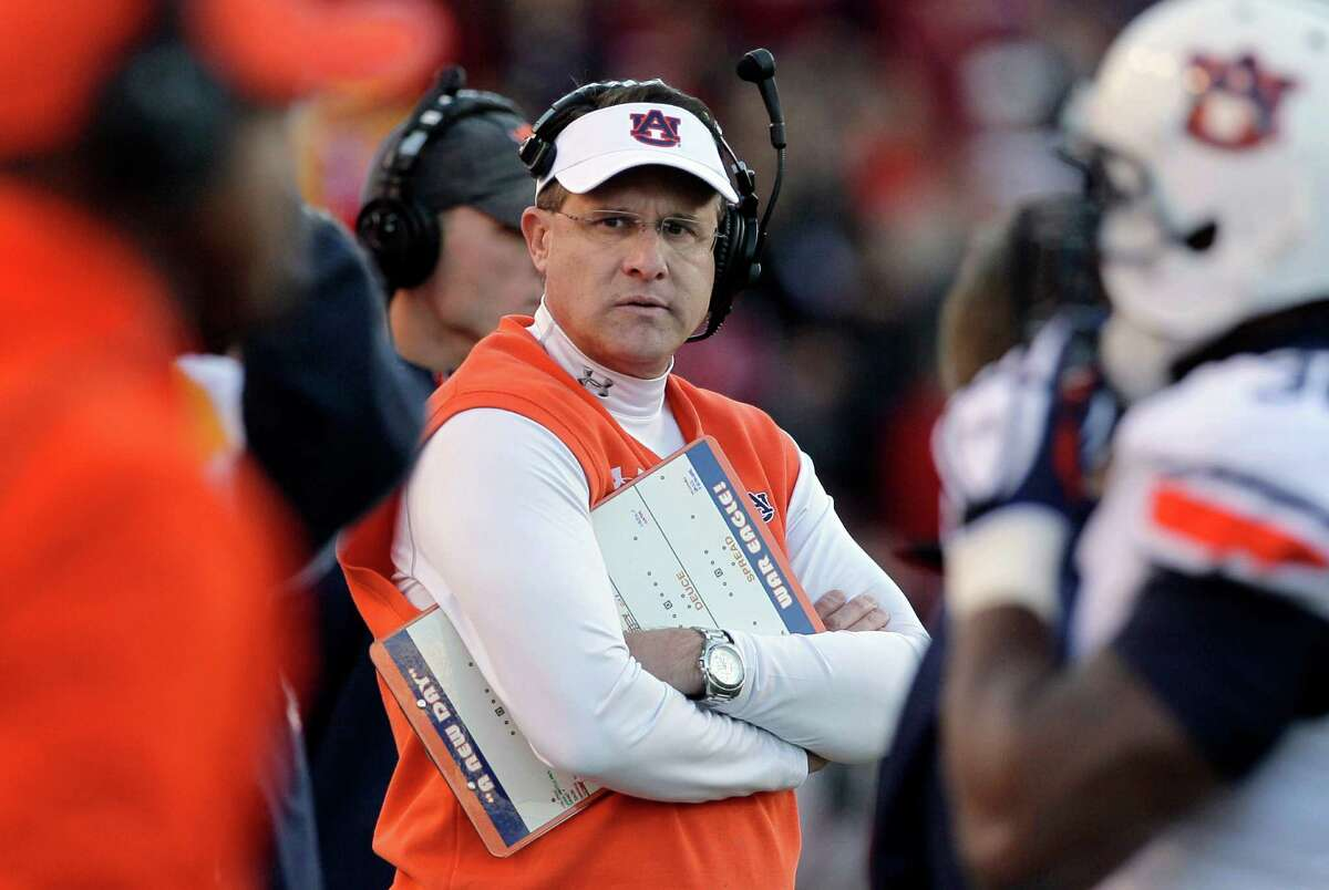 FILE - In this Nov. 2, 2013, file photo, Auburn coach Gus Malzahn, center, watches the first half of an NCAA college football game against Arkansas in Fayetteville, Ark. Malzahn led the second-ranked Tigers' transformation into Southeastern Conference champions and has them in the national championship game Jan. 6 against No. 1 Florida State. Malzahn's quick work made him The Associated Press national coach of the year. (AP Photo/Danny Johnston, File) ORG XMIT: NY186