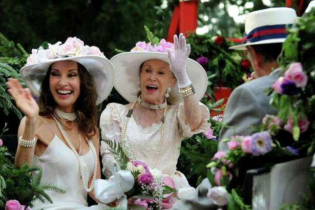Marylou Whitney, center, and Susan Lucci, left, wave to their adoring fans during an Old Fashioned Floral Fete Promenade to celebrate 150 years of thoroughbred racing Friday, Aug. 2, 2013, in Saratoga Springs, N.Y. (Cindy Schultz / Times Union)