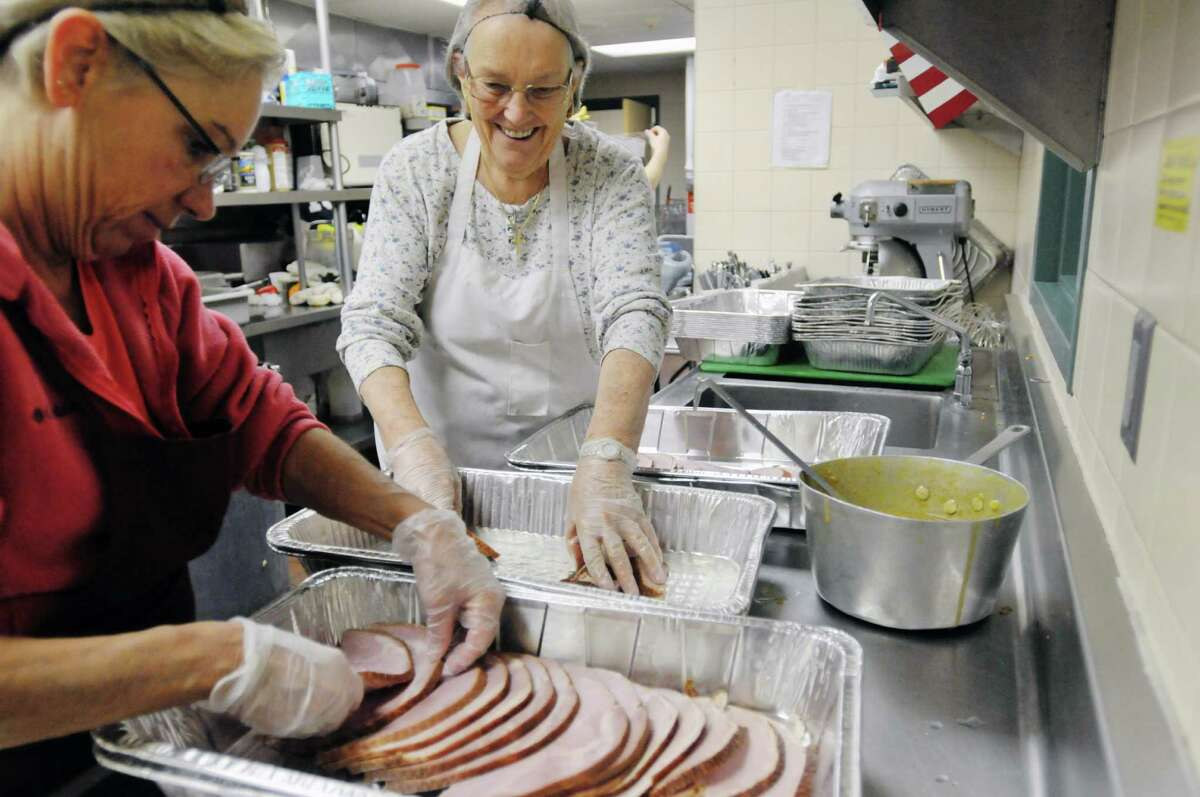 Volunteers Kim Blanchard, left, from Clarksville and Sue Hurd from East Greenbush lay slices of ham into baking dishes in preparation for Christmas day meal at the Capital City Rescue Mission on Monday, Dec. 23, 2013 in Albany, NY. The mission is preparing enough food for 3,300 meals this year, up from last year when 2,850 meals were prepared. Blanchard has volunteered for the past five years at Thanksgiving and this is the first year she has volunteered for Christmas. Hurd has been volunteering for the past ten years. (Paul Buckowski / Times Union)