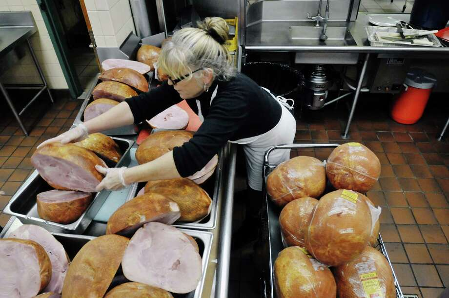 Volunteer Marie Fahey-Parker of Raven stacks a ham as another volunteer was quickly slicing up the hams for the Christmas day meal  at the Capital City Rescue Mission on Monday, Dec. 23, 2013 in Albany, NY.  Fahey-Parker, who is volunteering for the first time at the mission also brought along her son and his wife who are in from Alaska for the holiday.  The mission is preparing enough food for 3,300 meals this year, up from last year when 2,850 meals were prepared.    (Paul Buckowski / Times Union) Photo: PAUL BUCKOWSKI / 00025133A