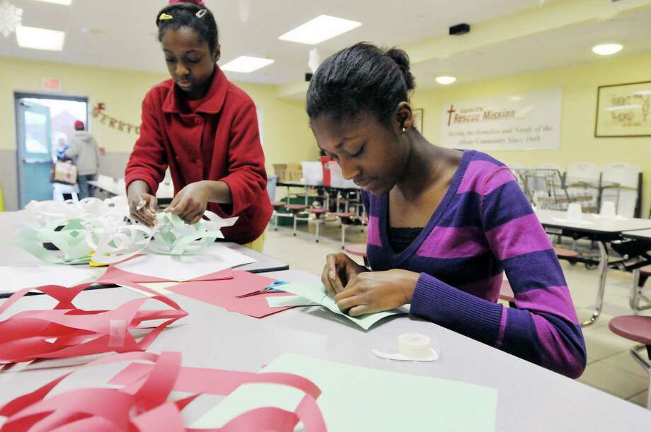 Sisters, Sarah Ansong, left, 11,  and Jenny Ansong, 14, hand make Christmas decorations for the Christmas day meal at the Capital City Rescue Mission on Monday, Dec. 23, 2013 in Albany, NY.  The two girls are the daughters of the mission's executive chef Max Ansong.  The mission is preparing enough food for 3,300 meals this year, up from last year when 2,850 meals were prepared.    (Paul Buckowski / Times Union) Photo: PAUL BUCKOWSKI / 00025133A