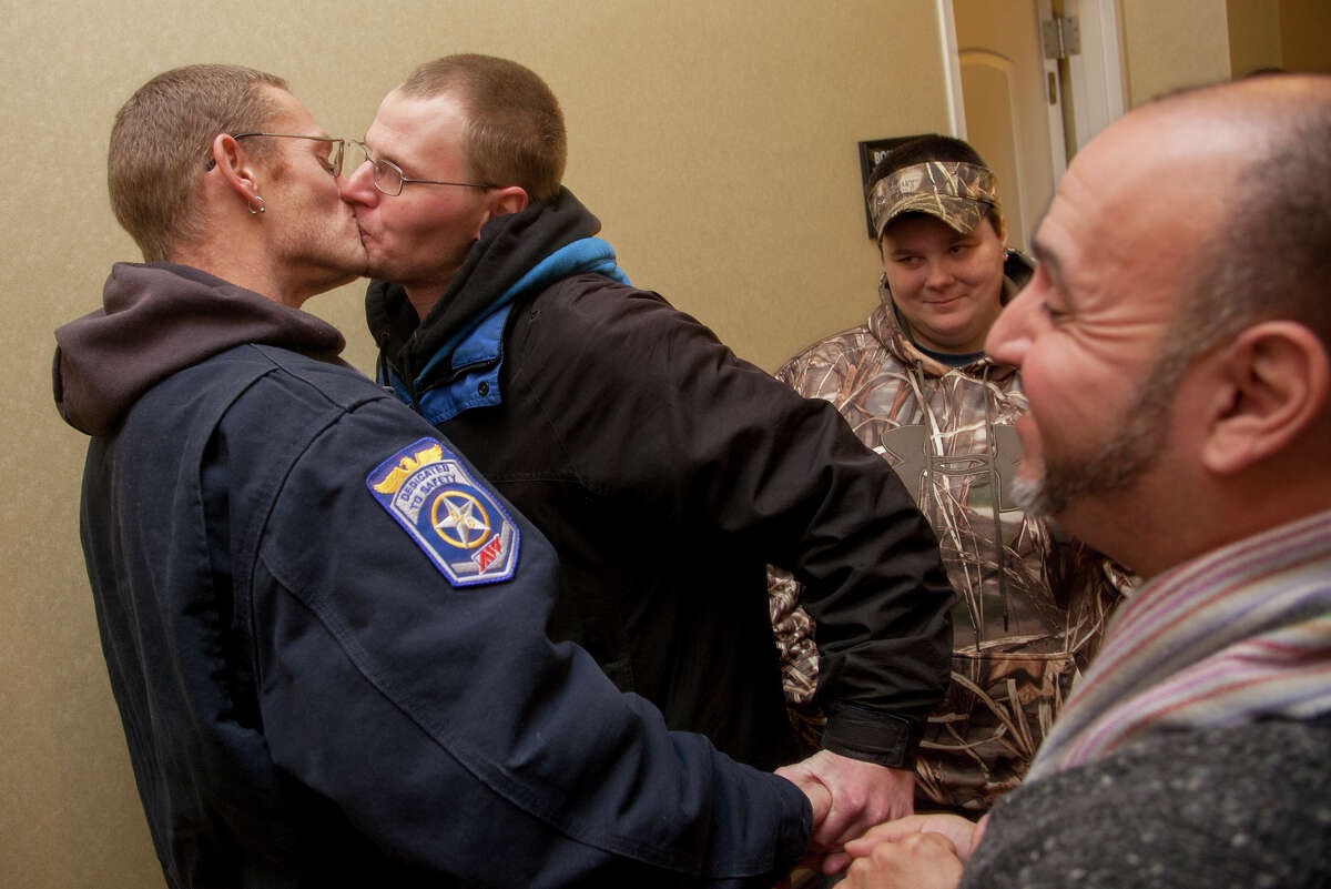 Patrick Freideman, left, and his husband Spencer Freideman kiss during their wedding in a hallway at the Hampton Inn in Ogden on Monday, Dec. 23, 2013. The Freidemans arrived at the county clerk's office on Sunday and spent the night on the sidewalk outside in order to make sure they had a chance to get married in Utah. (AP Photo/Standard-Examiner, Benjamin Zack) ORG XMIT: UTOGD104