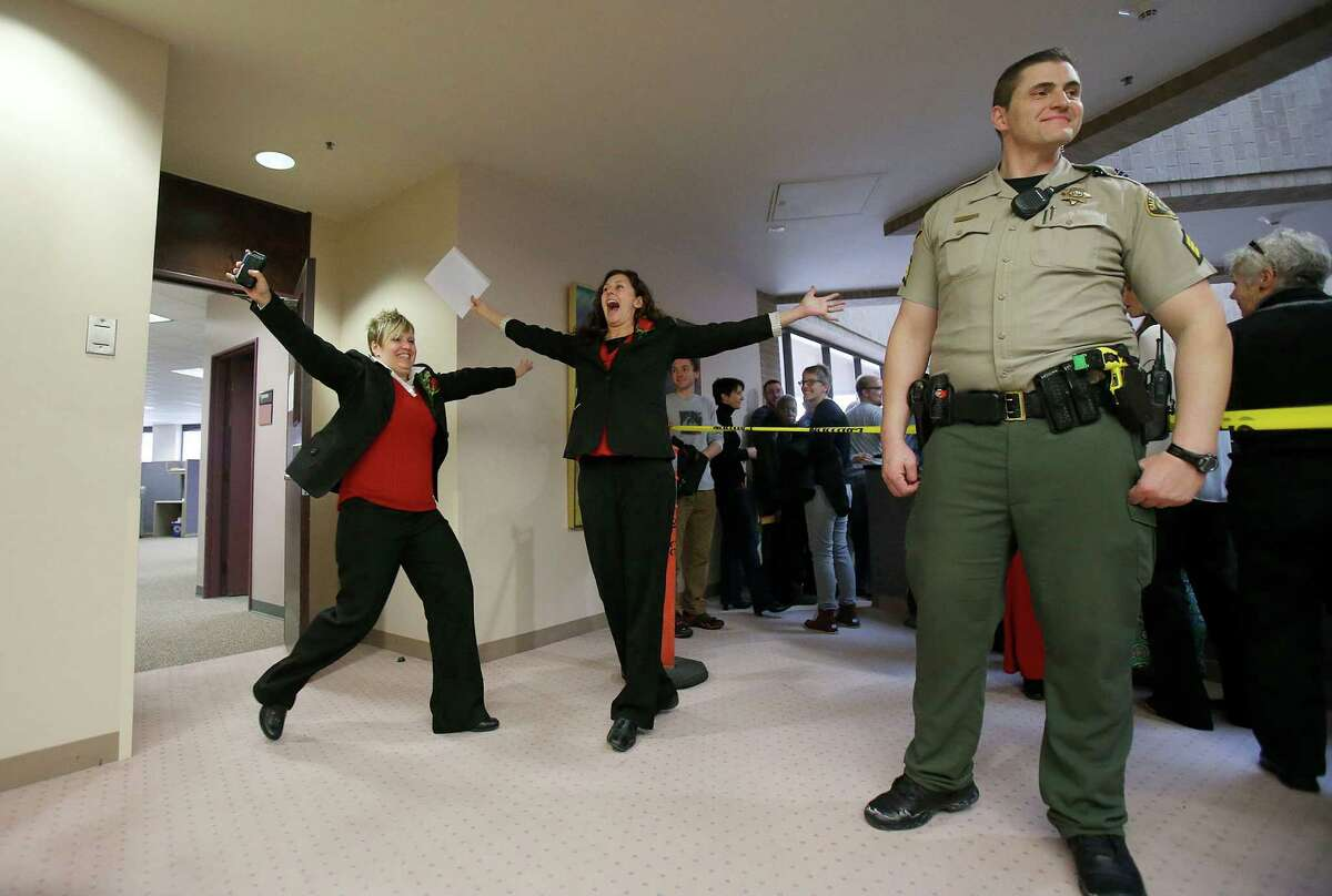 Becky Dustin, left, and Jennifer Rasmussen, right, exit the Salt Lake County clerk's office with their marriage license Monday, Dec 23, 2013. A federal judge said he will allow gay marriage in Utah to continue, denying a request from the state to halt same-sex weddings until the appeals process plays out. (AP Photo/Deseret News, Ravell Call) ORG XMIT: UTSAL104