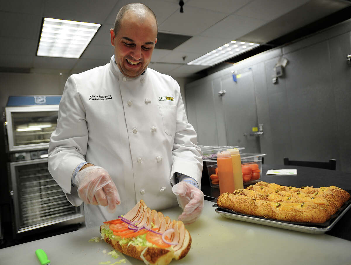 Corporate Executive Chef Chris Martone builds a footlong turkey sub on the company's new jalapeno cheese bread in the test kitchen at Subway headquarters in Milford, Conn. on Monday, December 23, 2013.