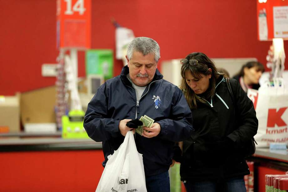 A customer sorts through cash after checking out at a Kmart in New York last month. Photo: Julio Cortez, STF / AP
