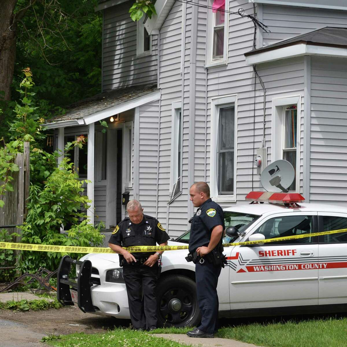 Washington County Sheriff's Deputy Ron Thomas, left, and Patrolman Matt Jackson of the Fort Edward Police Dept. in front of 8 Keating Avenue in Fort Edward Wednesday, June 6, 2012. Authorities say a Gary Cota, 13, died in an accidental shooting in the house. (John Carl D'Annibale / Times Union)