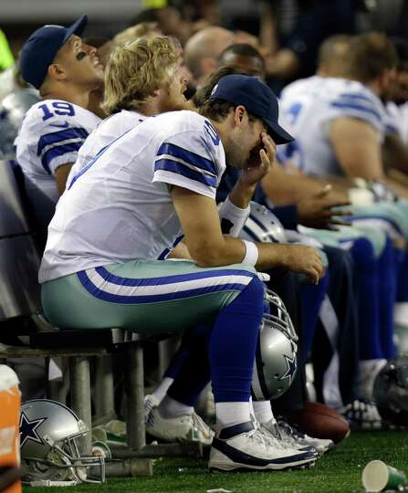 Dallas Cowboys quarterback Tony Romo sits on the bench in the final minutes of the second half of an