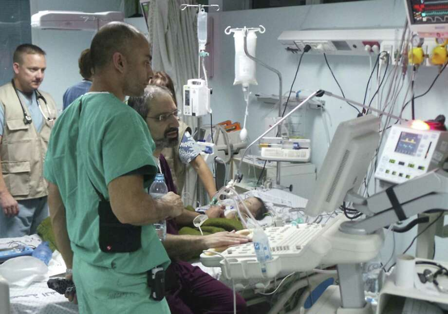 San Antonio Drs. S. Adil Husain (in green) and Roozbeh Taeed (in maroon), work near 4-month-old Nada Hamdan after surgery to repair her heart defect. Photo: Courtesy Photo