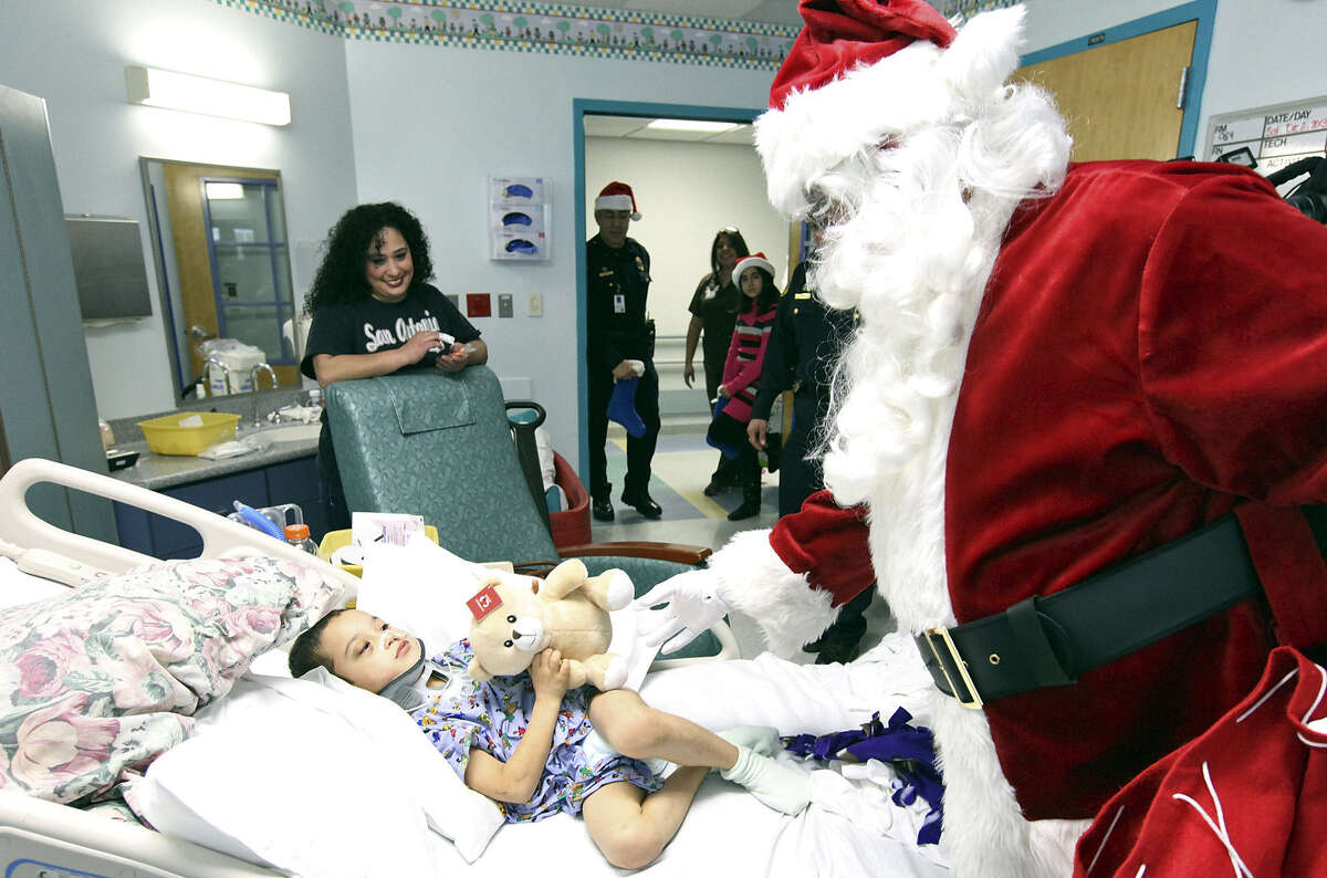 Six-year-old Andres Garcia gets a teddy bear from Santa as the young patient's mom, Esmeralda Garcia, watches her son's reaction.