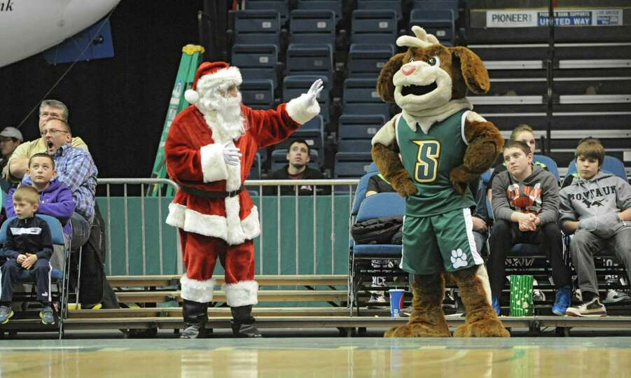 Saint Nick waves at the Siena Saint Bernard mascot during a basketball game against Hofstra at the T