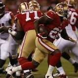 San Francisco 49ers running back Frank Gore (21) picks up yardage in the first quarter of Monday night's game against the Atlanta Falcons on Dec. 23, 2013 in San Francisco, Calif.