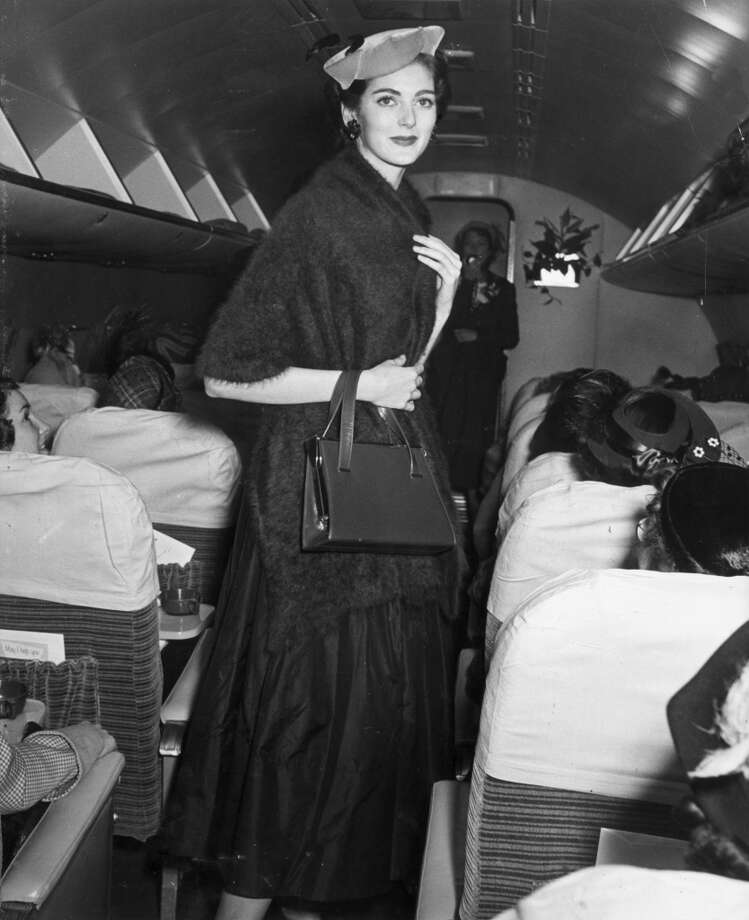 American model Carmen Dell'Orefice while walking in the aisle of an airplane during a fashion show, circa 1955. Photo: Hulton Archive, Getty Images