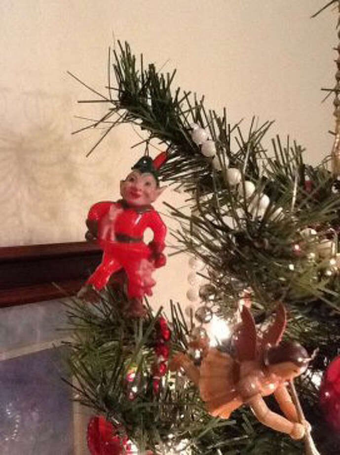 "Nina Stansel Zoch, Deer Park: This ""Creepy Elf"" (so called by my daughter) is the last remaining ornament from the childhood trees in my mother's house in Pasadena, then Deer Park.  A little scary, but he is carrying a toy deer and a doll. Not many survived the ruckus of 5 siblings divided into armed camps over hanging versus throwing the silver icicles onto the long-needle pine Christmas tree chopped down by my father while deer hunting.  That was followed by wrapping-paper roll fights that lasted until the last piece of cardboard was in shreds."