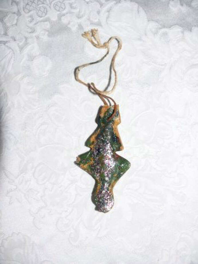 """Penny Dollahon, Houston: We were living in Hawaii at Ewa Beach Naval Base in 1976. At the little community preschool our first son, Walker, made this """"cookie"""" ornament for our Christmas tree. I never dreamed it would last so many years - he is now the father of 5! Love the glitter, love the paint job at the hands of our three-year-old. Treasure it above all other ornaments!"""