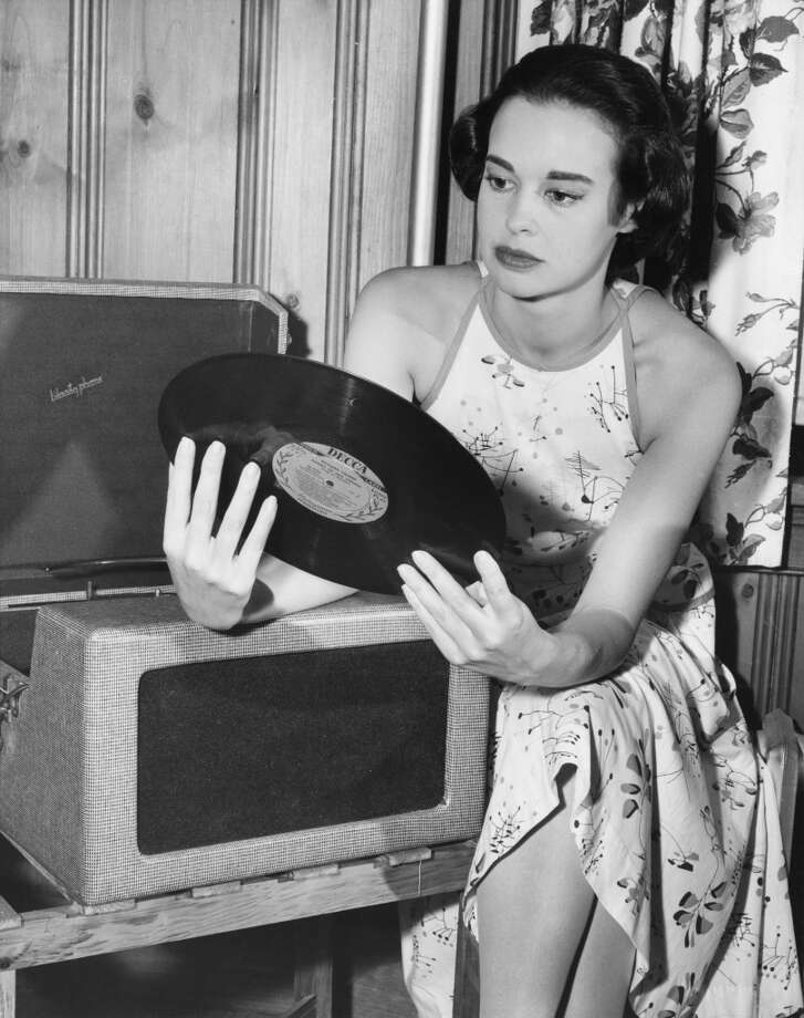 American socialite, fashion designer, actress, writer and artist Gloria Vanderbilt with a Decca long-play record by Richard Tauber entitled 'Songs of Old Vienna', August 1954. Photo: Archive Photos, Getty Images