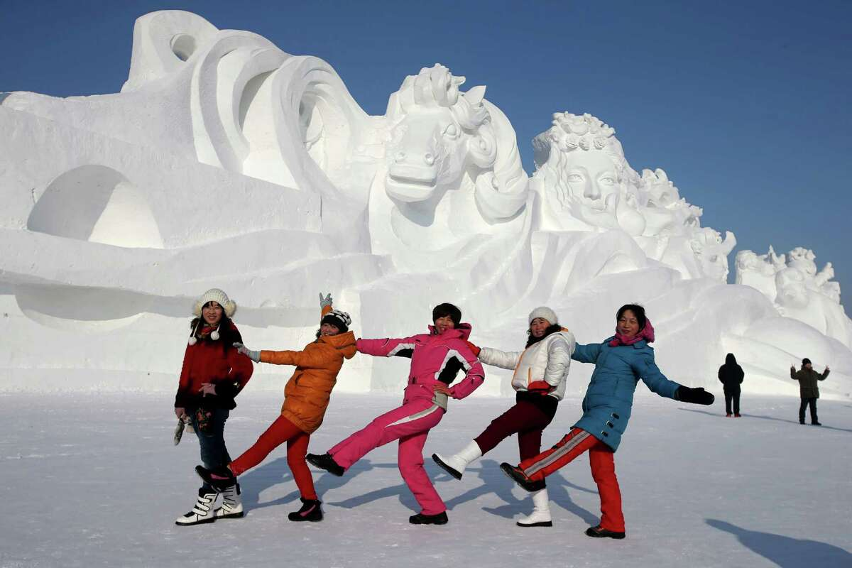 Harbin, China, has one of the world's largest ice and snow festivals in the world. These folks strike a pose in front of a 117-meter-long, 26-meter-high sculpture at the 26th Harbin International Snow Sculpture Art Expo in Sun Island park on Sunday.
